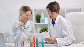 Two female chemist wearing uniform and protective glasses looking on paper document in lab. Two female chemist wearing uniform and protective glasses looking on stock video