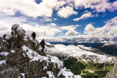Two female climbers on a snowy and exposed ridge in the Dolomites. Two female climbers on a snowy and exposed ridge on a Via Ferrata in the South Tyrol in the Royalty Free Stock Images