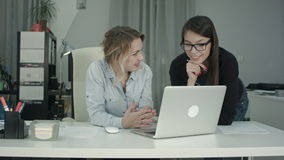 Two female colleagues discussing new project idea using laptop stock footage