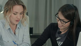 Two female colleagues happily discussing new project in the office. Closeup shot. Professional shot on BMCC RAW with high dynamic range. You can use it e.g. in stock video footage