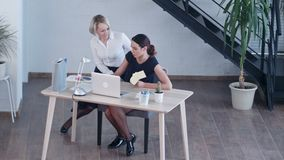Two female colleagues talking in office. Professional shot in 4K resolution. 091. You can use it e.g. in your commercial video, business, presentation stock video
