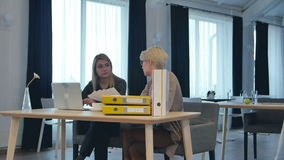 Two female colleagues talking in office. Professional shot in 4K resolution. 090. You can use it e.g. in your commercial video, business, presentation stock video footage