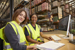 Two female colleagues in a warehouse office look to camera stock image