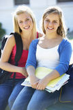 Two Female College Students Sitting On Bench With Textbook Stock Photo