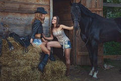 Two female cowboys on a farm with horses. Two female cowboys on a farm with horses sitting on a straw royalty free stock photography