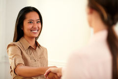 Two female coworkers giving hands greeting Stock Photo
