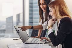 Two female coworkers pointing at laptop screen and laughing during working process in modern office.  stock photo