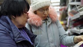 Two female customers choose kitchen accessories in the hardware store. Two female customers choose kitchen accessories in the tableware department of the