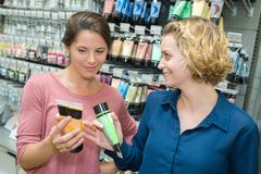 Two female customers selecting haircare products in drugstore. 2 royalty free stock photography