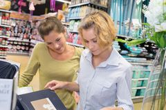 Two female customers selecting haircare products in drugstore. 2 stock images