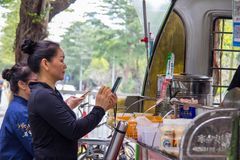 Two female customers use smartphone to pay their breakfast at a street booth with Qr code. Shenzhen, China - November 14 2018: Two female customers use stock photography