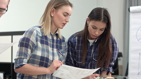 Two female designers discussing layout and color samples stock video