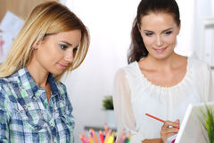 Two female designers in office looking at laptop Stock Image