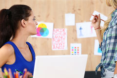 Two female designers in office looking at wall Stock Photos