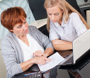 Two female discussing documents at home Royalty Free Stock Photography