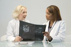 Two Female Doctors. Two women doctors reviewing an MRI scan in an office Royalty Free Stock Images