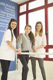Two female doctors helping girl to walk Stock Images