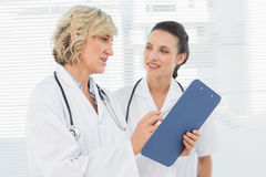 Two female doctors reading medical reports Royalty Free Stock Photos