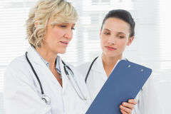 Two female doctors reading medical reports Stock Images