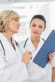 Two female doctors reading medical reports Stock Photos