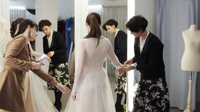 Two female dress designers and a beautiful bride trying her wedding gown in elegant boutique or tailor`s studio. A woman