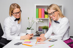 Two  female employees working together Stock Photos