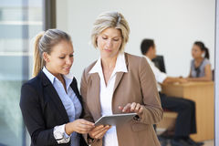 Two Female Executives Looking At Tablet Computer With Office Meeting In Background Stock Photography