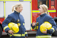 Two female firefighters by a fire engine Stock Photography