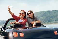 Two female freinds take a selfie photo in cabriolrt car during t. Heir summer voyage royalty free stock photos