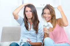 Two female friend playing on games console. Two female friend playing on a games console Royalty Free Stock Photography