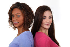 Two female friends. Stood back to back Stock Photos