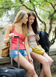 Two female friends with baggage using the map Royalty Free Stock Image