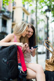 Two female friends with baggage using the navigator Royalty Free Stock Photos
