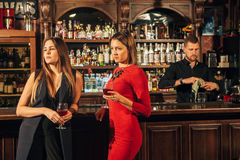 Two female friends are in the bar for a drink and talk. The woman with talks near the ear of the friend Royalty Free Stock Image