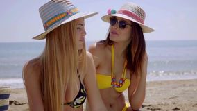 Two female friends on a beach in the summer. Two female friends wearing swim suits and sun hats on a beach by the ocean in the summer stock video