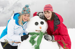 Two Female Friends Building Snowman On Ski Holiday Stock Photos