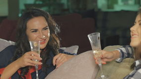 Two female friends chatting, drinking champagne on the sofa in room stock footage