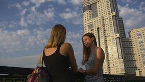 Two female friends chatting on the urban bridge. Two female friends talk standing on the urban bridge in front of modern building stock video