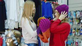 Two female friends choose warm clothes in a clothing store. Look at the scarf and hat. Shopping for winter stock footage