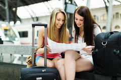 Two female friends with city map. And luggage at railway station Stock Images