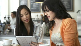 Two Female Friends In Coffee Shop Looking At Digital Tablet stock video footage