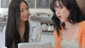 Two Female Friends In Coffee Shop Looking At Digital Tablet stock video
