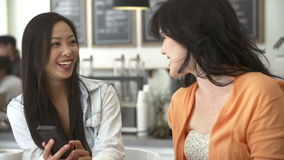 Two Female Friends In Coffee Shop Looking At Mobile Phone stock footage