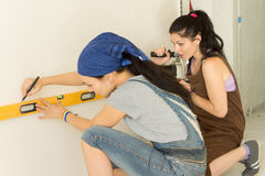 Two female friends doing DIY at home. Working as a team with one marking the wall with a spirit level while the second handles the electric drill Royalty Free Stock Photo