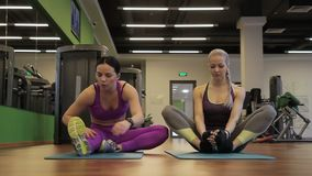 Two female friends are doing stretching exercises before yoga class in modern gym. Blond woman is sitting on green mat in bound angle pose and brunette lady in stock footage