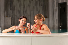 Two female friends drinking tea in swimming pool. They doing wellness in their vacation Royalty Free Stock Photos