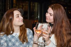 Two female friends drinking wine. The close up of two female friends drinking white wine in restaurant Royalty Free Stock Photo