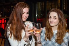 Two female friends drinking wine. The close up of two female friends drinking white wine in restaurant Stock Photography