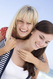 Two female friends embracing on beach Stock Photos