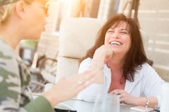 Two Female Friends Enjoying Conversation Outside. Two Female Friends Enjoying Conversation on the Patio Royalty Free Stock Images